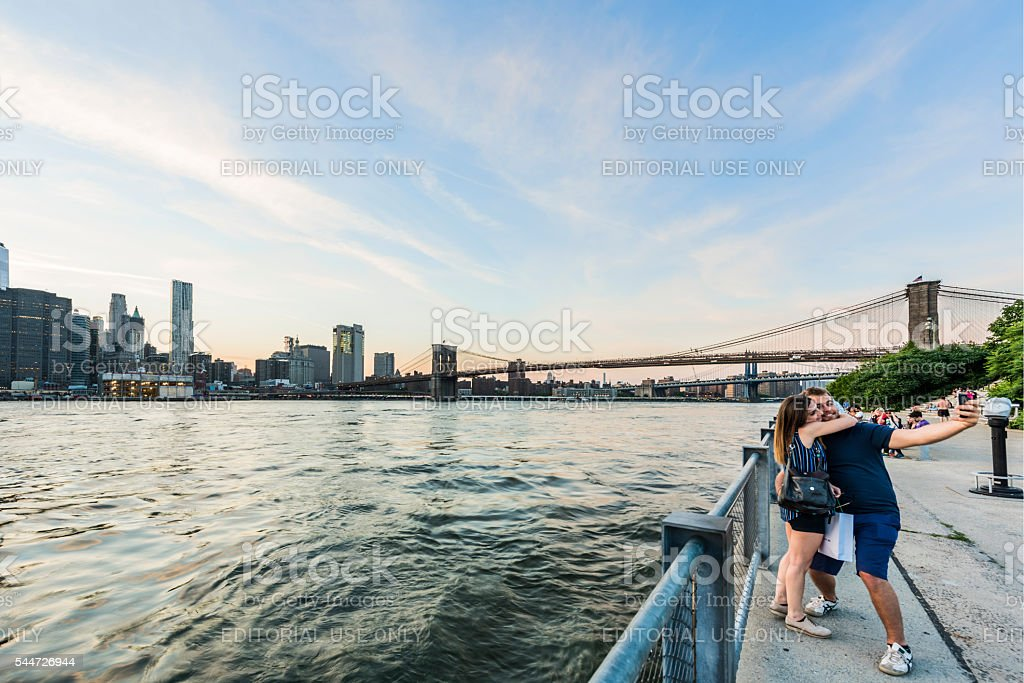 Couple taking a selfie at Brooklyn bridge park stock photo