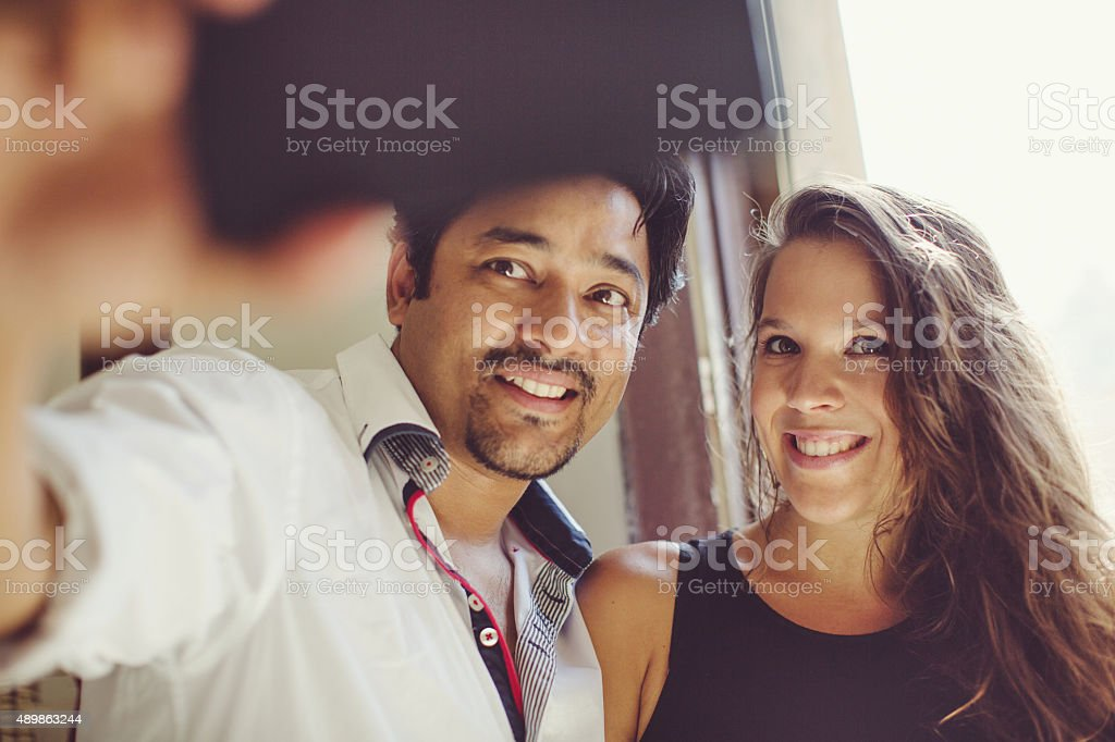 Couple taking a selfie by a window stock photo
