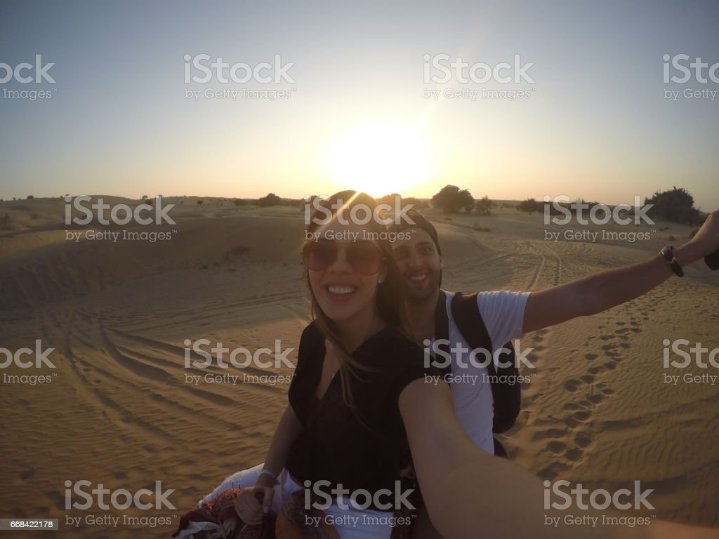 Couple taking a selfie in a camel riding in desert stock photo