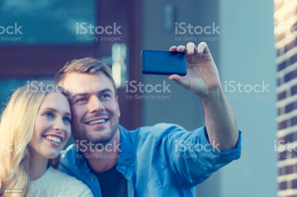 Couple taking a selfie in front of house. stock photo