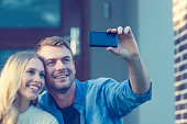 Couple taking a selfie in front of house.