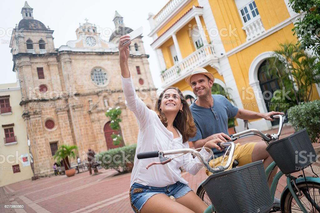 Couple taking a selfie while sightseeing on bikes stock photo