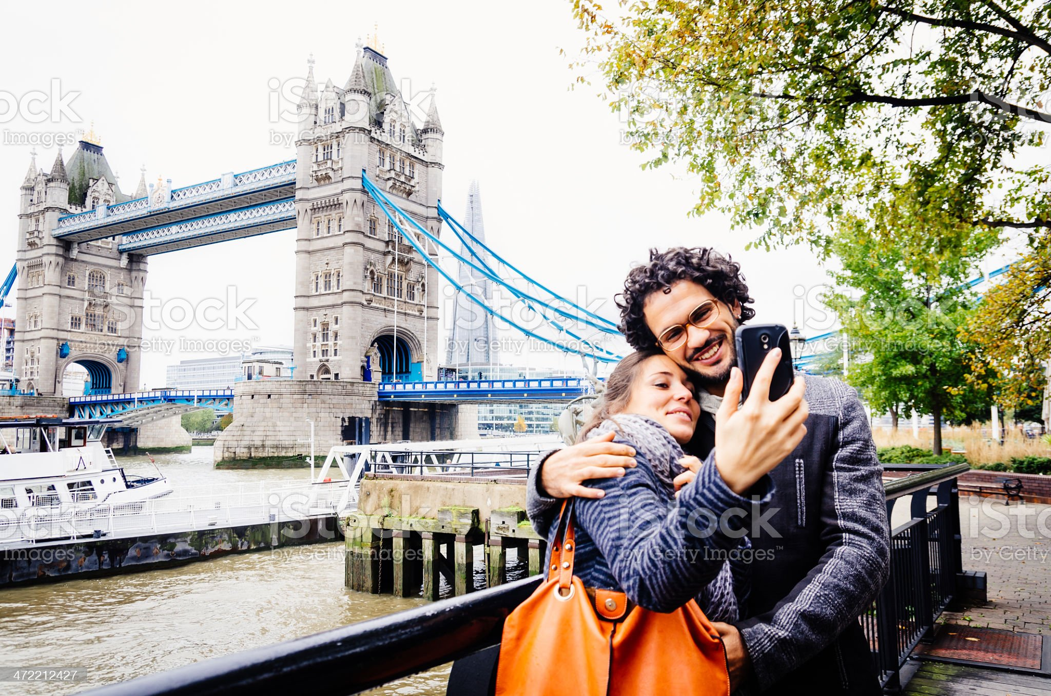 A couple taking a selfie with a phone in London by a bridge royalty-free stock photo