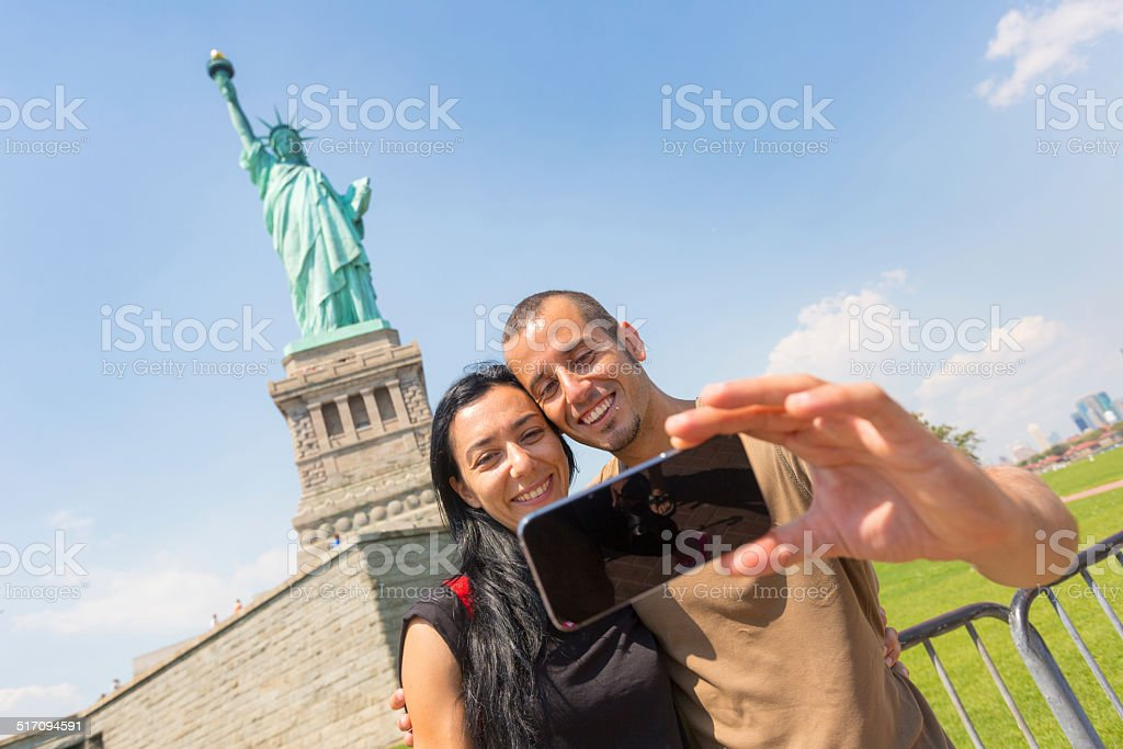 Couple Taking a Selfie with Statue of Liberty on Background stock photo
