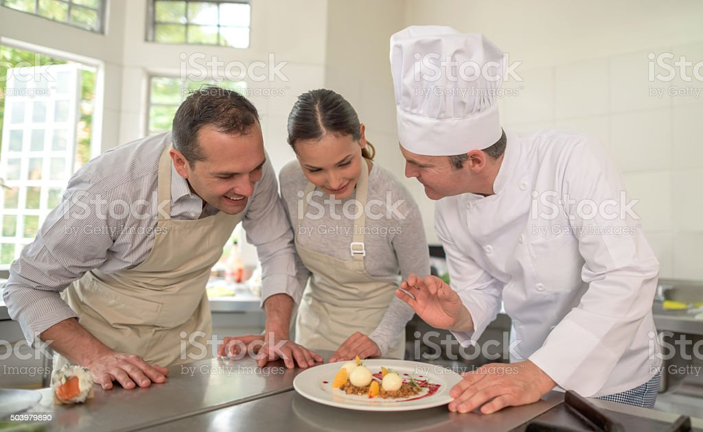 Couple taking cooking lessons stock photo
