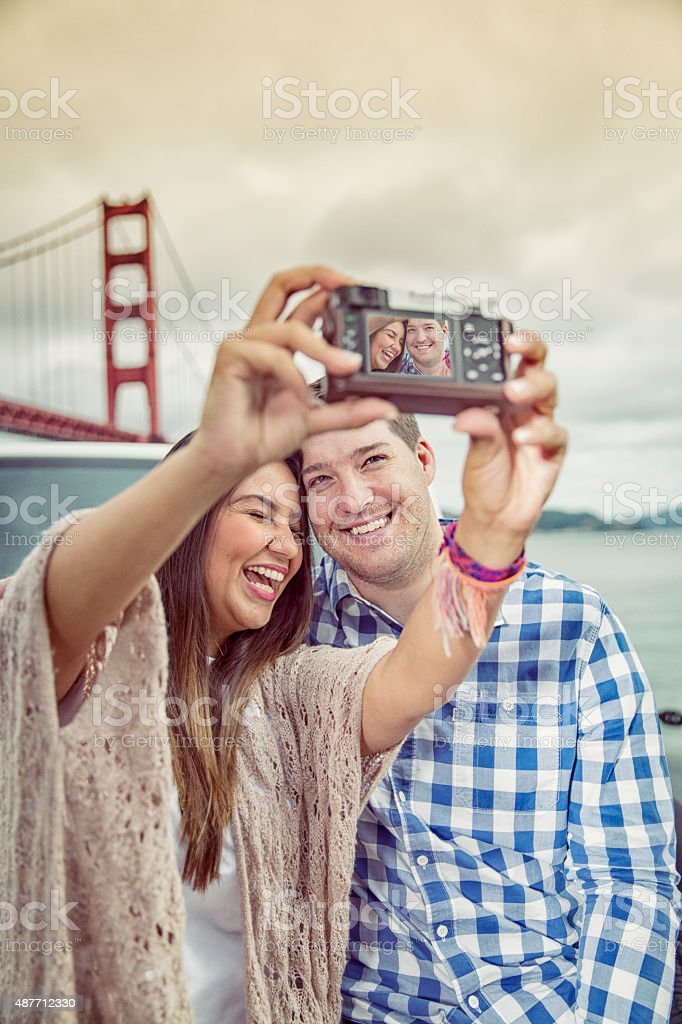 Couple Taking PIctures at the Golden Gate Bridge San Francisco stock photo