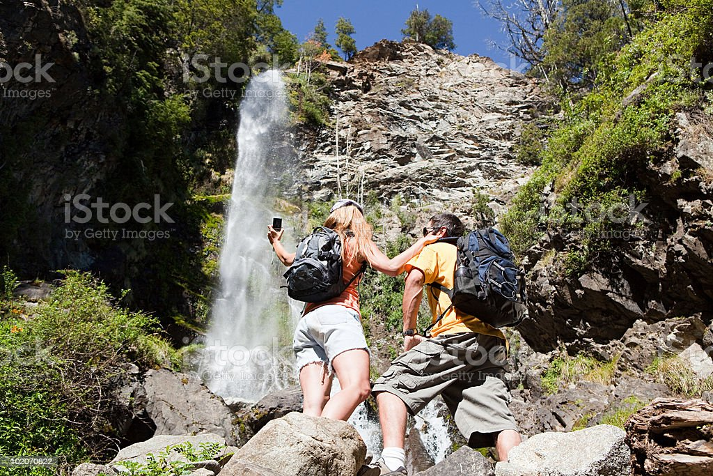 Couple taking pictures by waterfall royalty-free stock photo