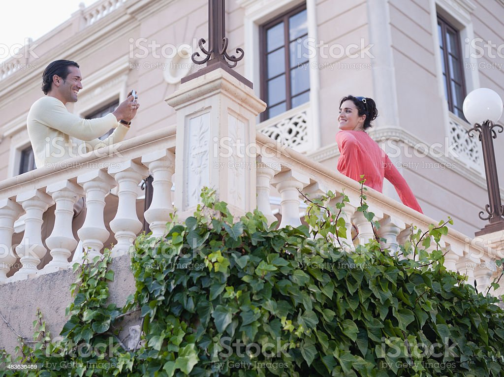 Couple taking pictures on balcony stock photo