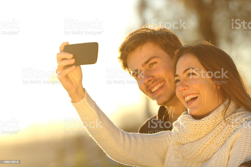 Couple taking selfie photo with a smart phone at sunset stock photo