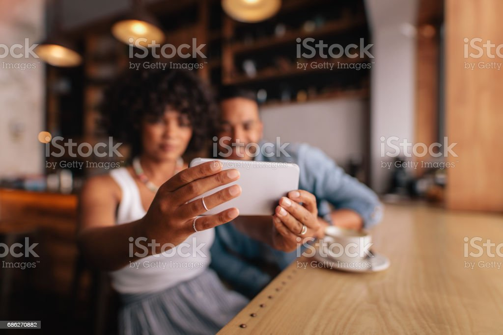 Couple taking selfie with smart phone at cafe stock photo