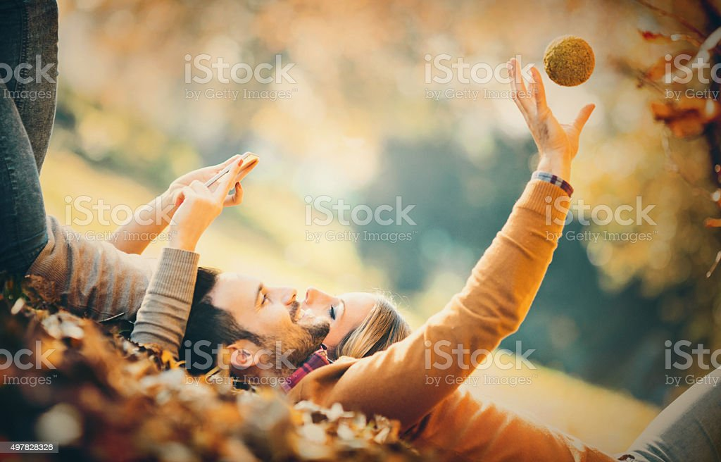 Couple taking selfies in a park. stock photo