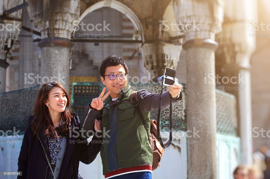 Couple taking selfies in front of Blue Mosque in Istanbul stock photo