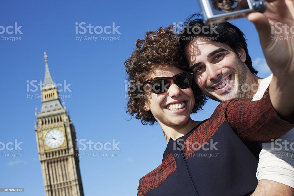 Couple taking self-portrait with digital camera below Big Ben clocktower in London royalty-free stock photo