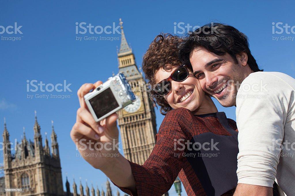 Couple taking self-portrait with digital camera below Big Ben clocktower in London royalty-free stock photo