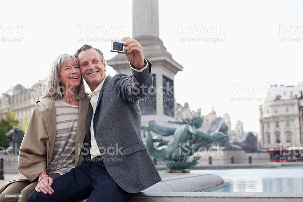 Couple taking self-portrait with digital camera under monument royalty-free stock photo