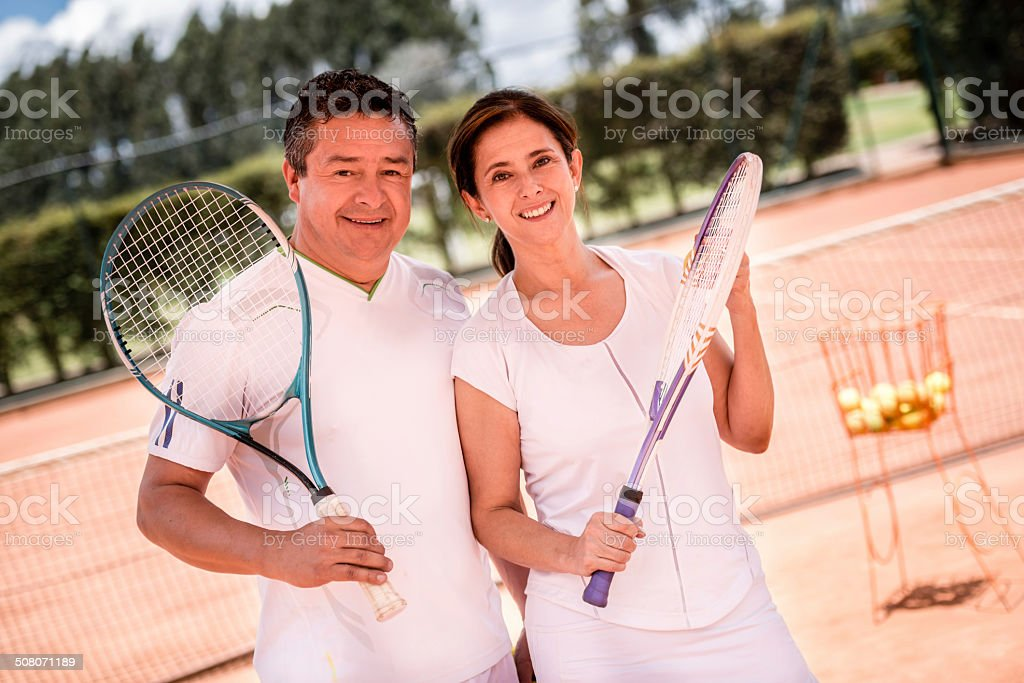 Couple taking tennis lessons stock photo