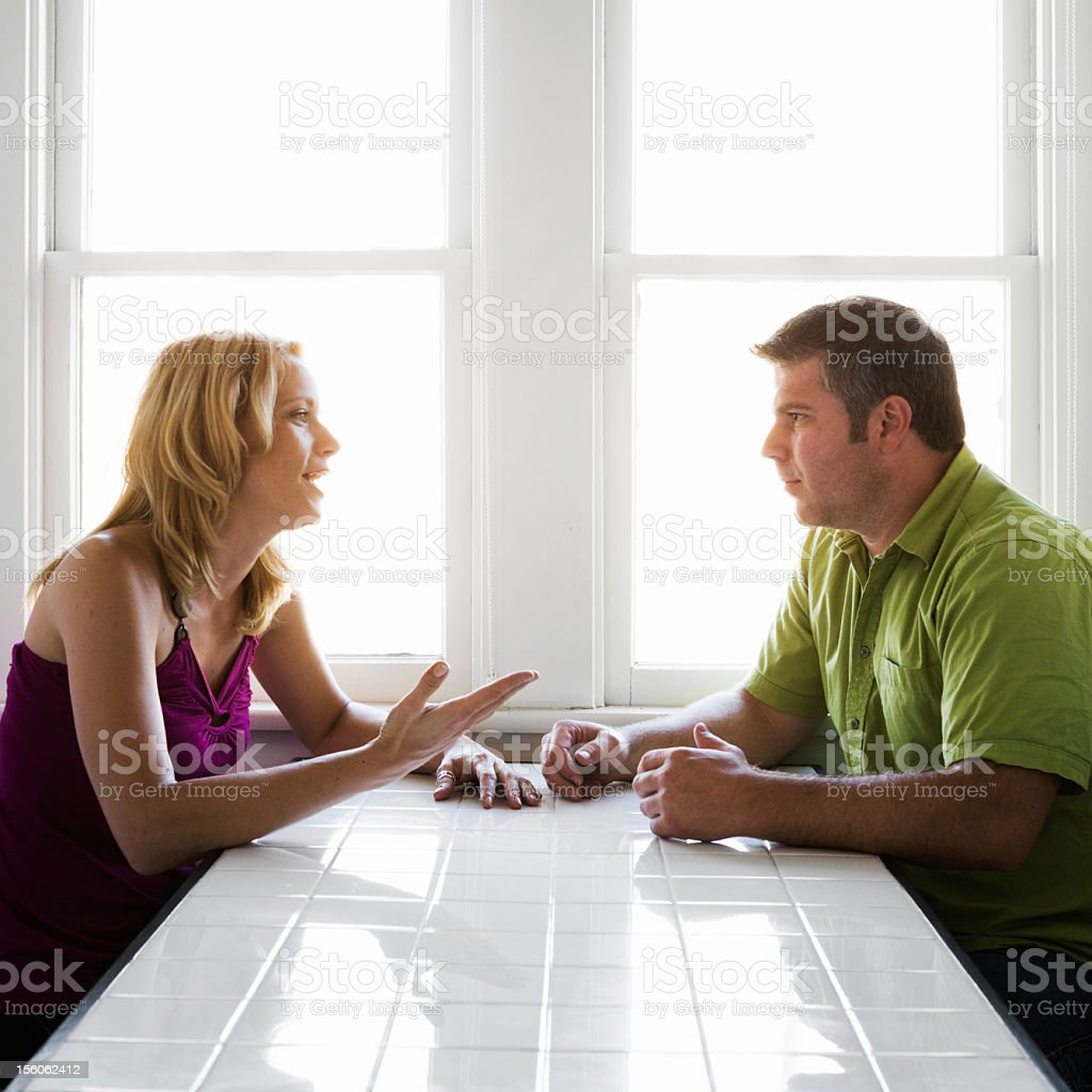 Couple Talking at Kitchen Table stock photo