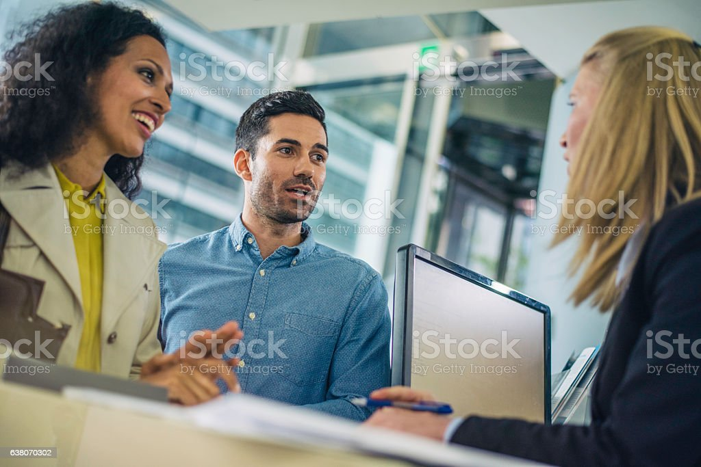 Couple talking to a bank teller stock photo