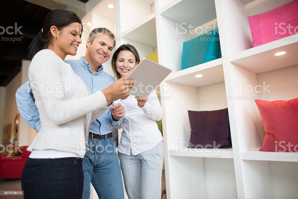 Couple talking to a saleswoman at a furniture store stock photo