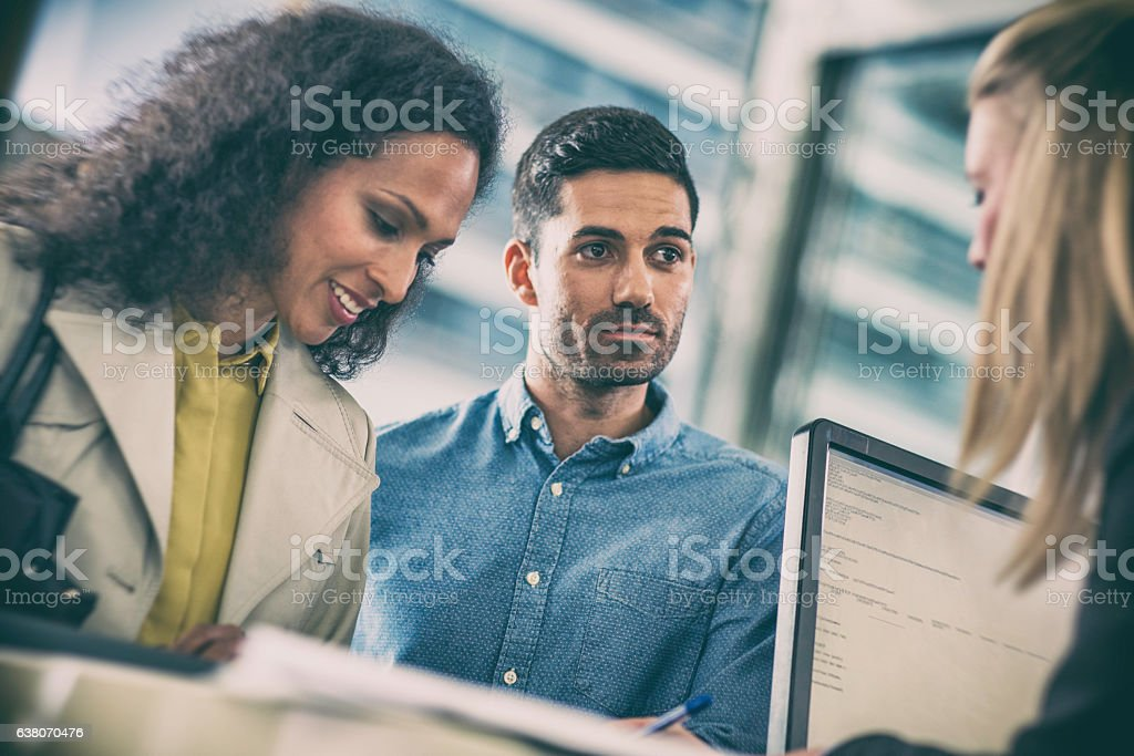 Couple talking to insurance agent at the counter stock photo