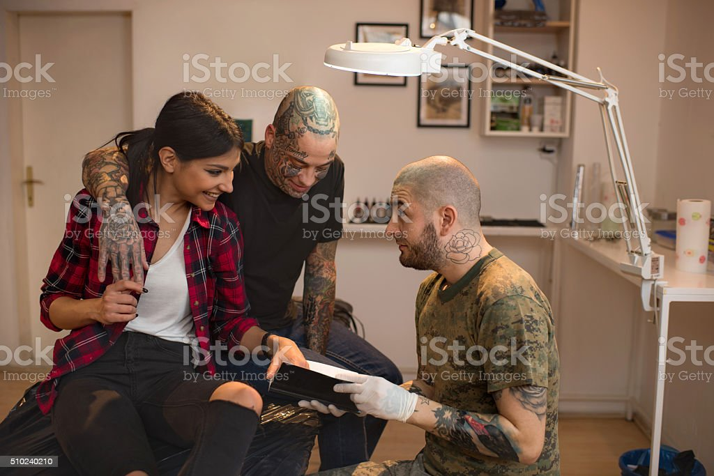 Couple talking to tattoo artist and looking at tattoo catalog. stock photo