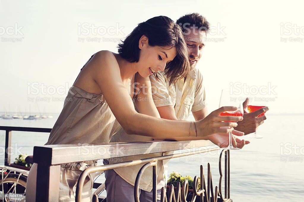 Couple talking while having spritz in a lake view terrace stock photo