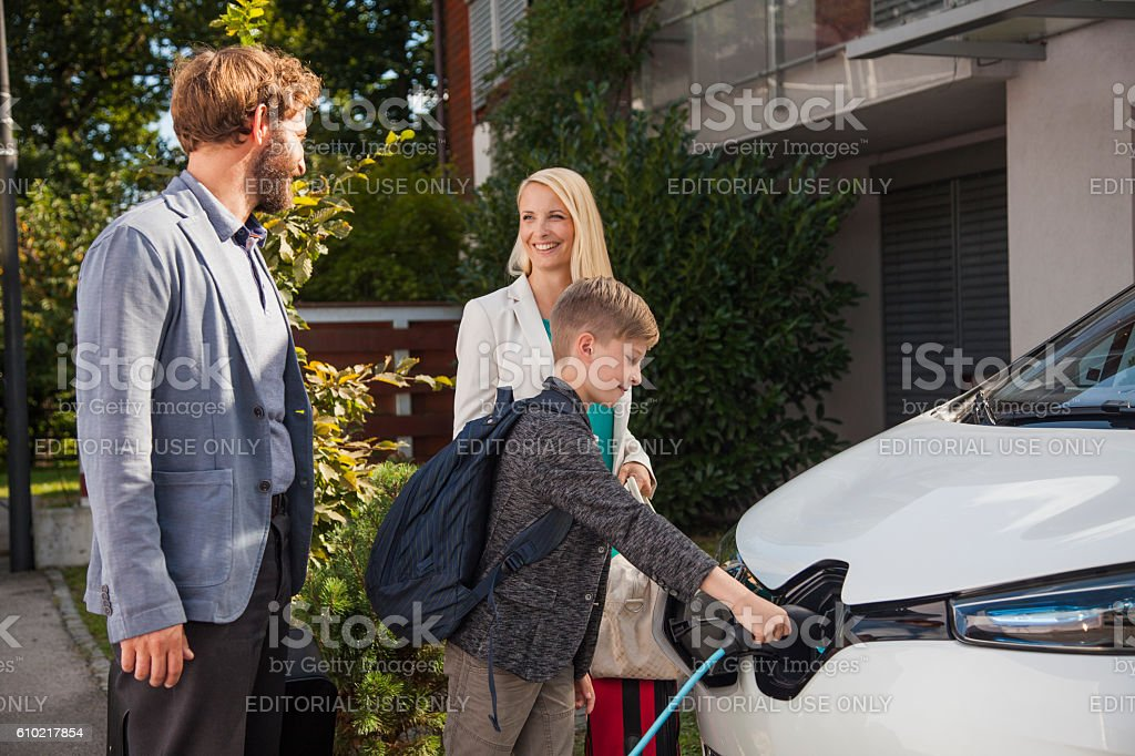 Couple talking while their son plugs in Renault Zoe stock photo