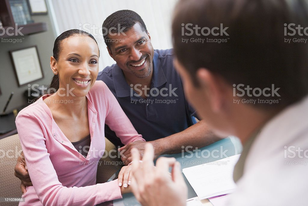Couple talking with doctor in IVF clinic stock photo