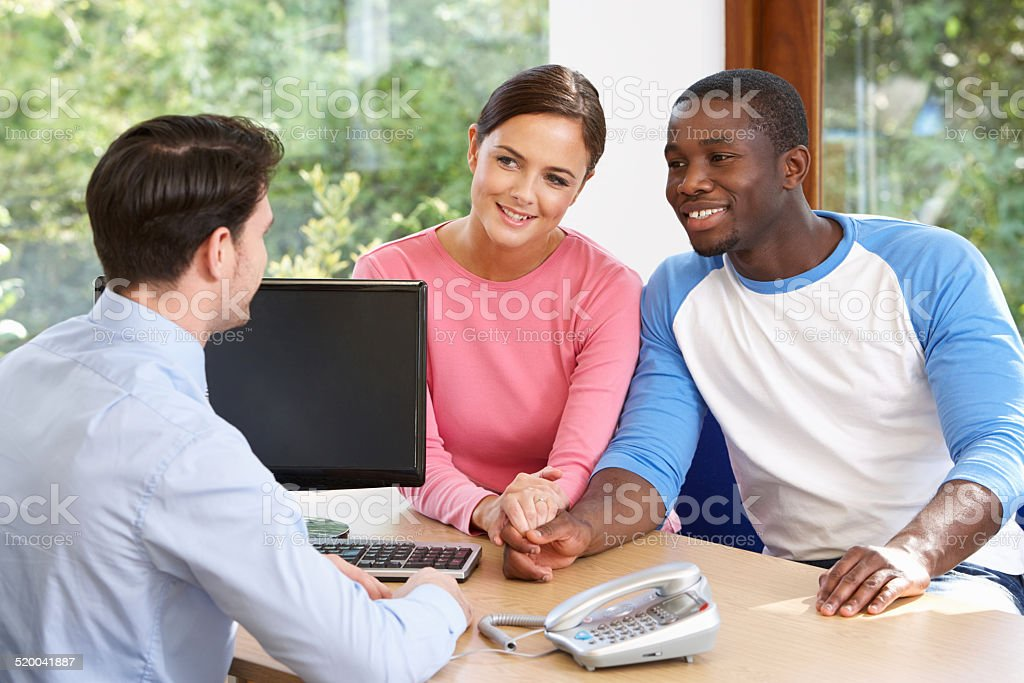 Couple Talking With Financial Advisor In Office stock photo