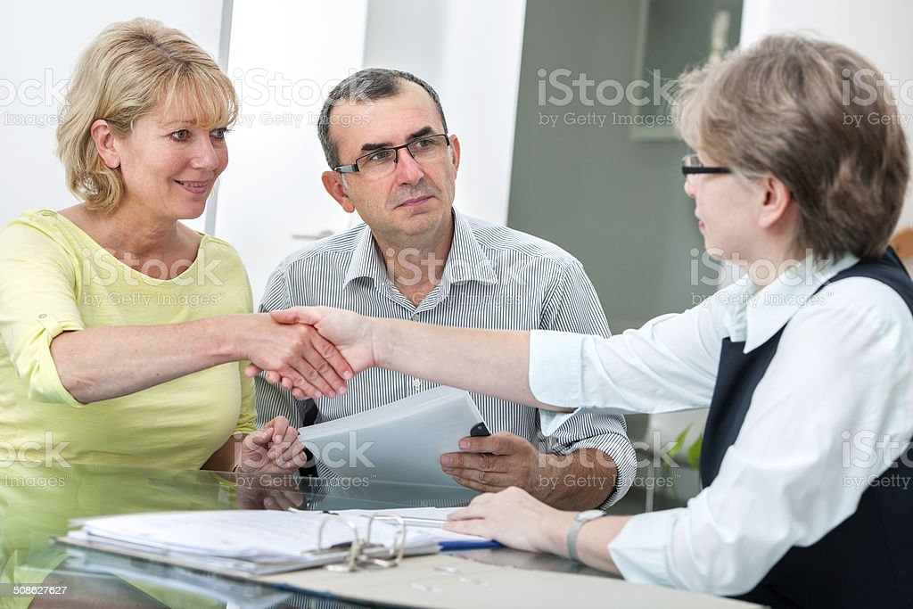 Couple talking with financial advisor stock photo