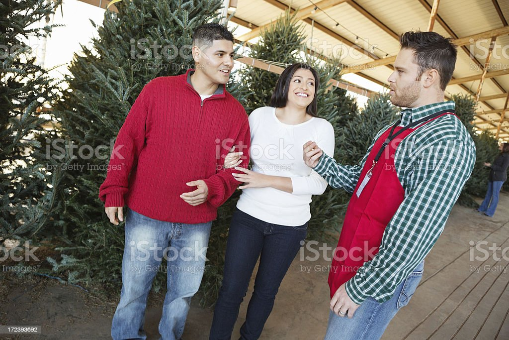 Couple talking with salesperson at Christmas tree farm stock photo