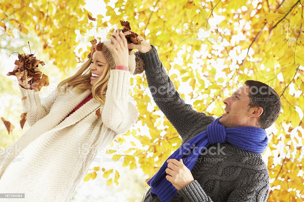 Couple Throwing Leaves In Autumn Garden royalty-free stock photo