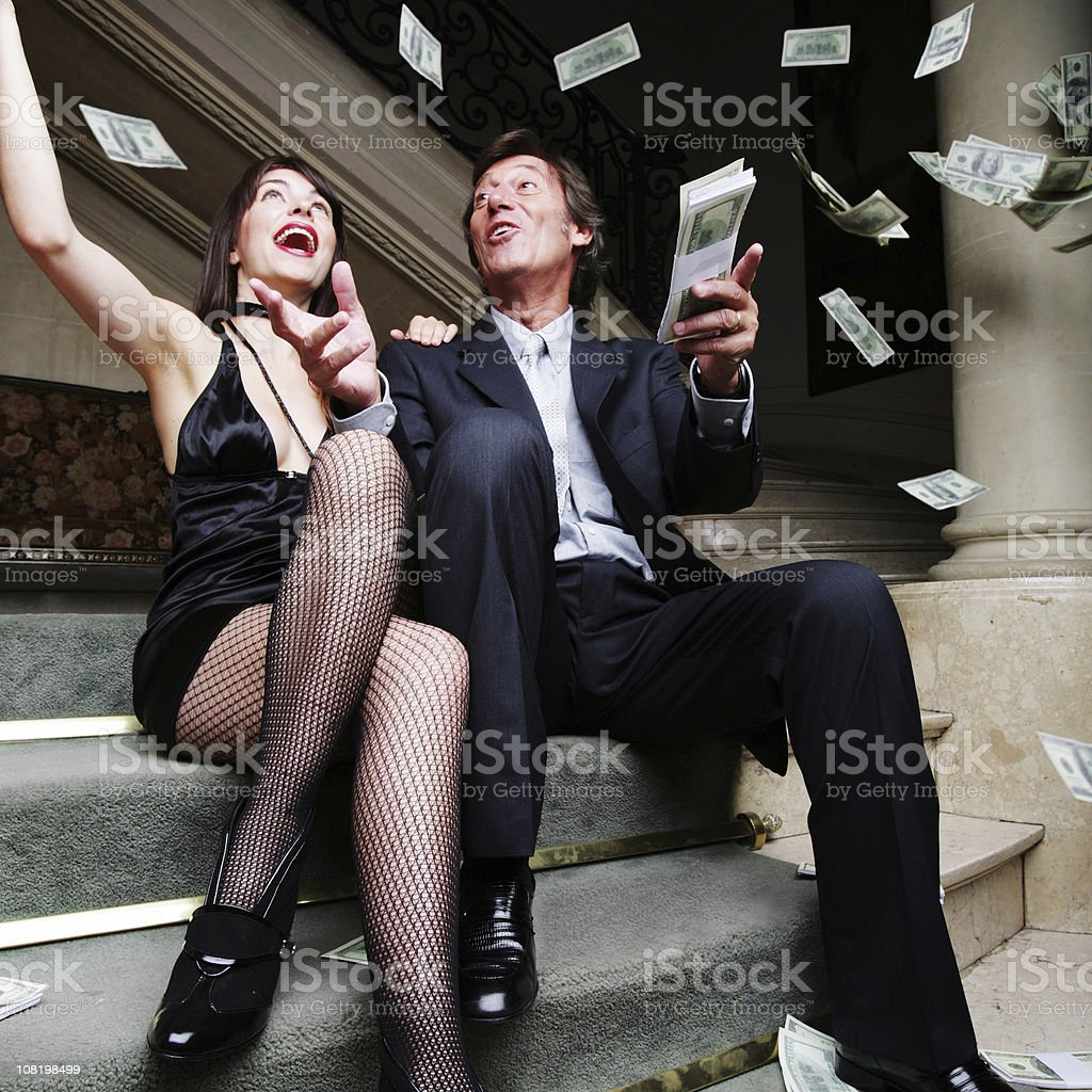 Couple Throwing Money in the Air stock photo