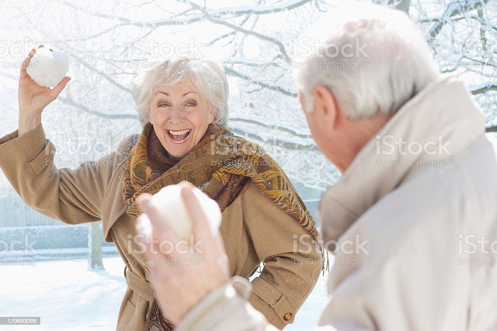 Couple throwing snowballs royalty-free stock photo