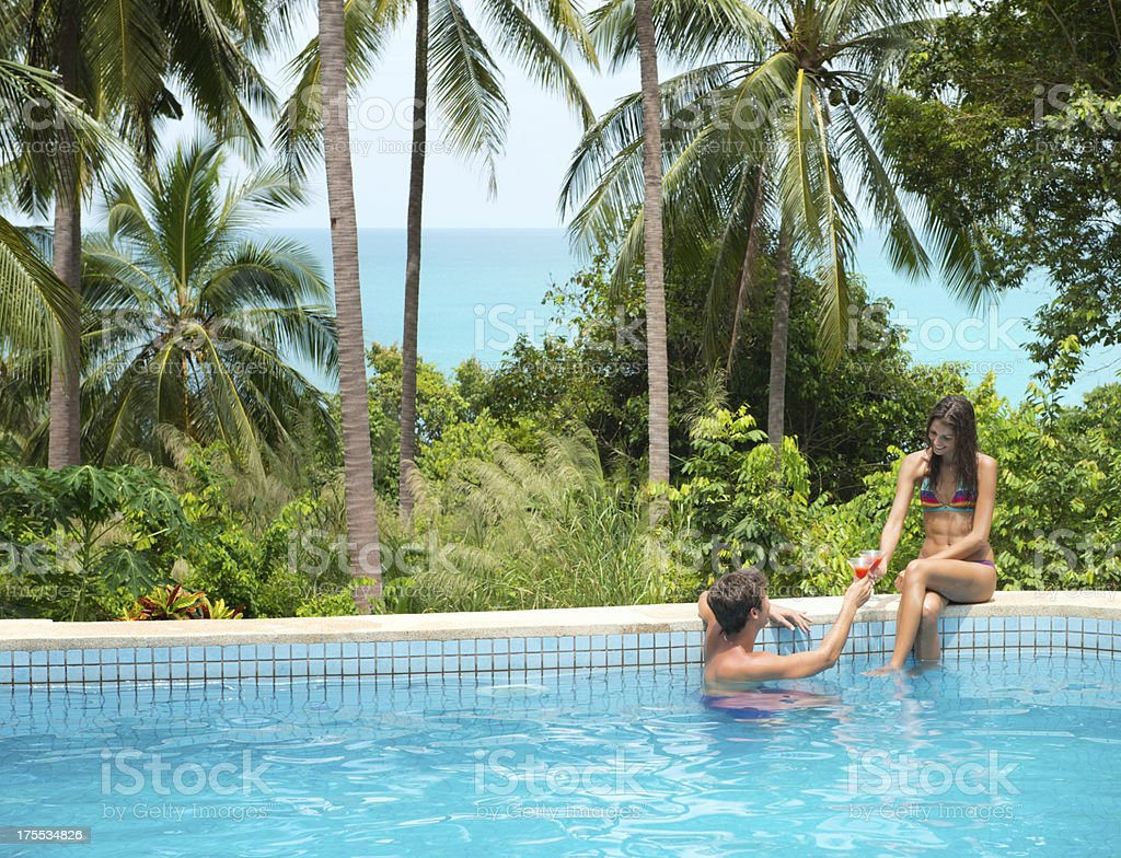 Couple toasting at the private Pool on Honeymoon (XXXL) royalty-free stock photo