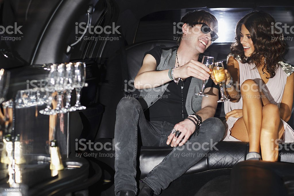 Couple toasting each other in backseat of limo royalty-free stock photo