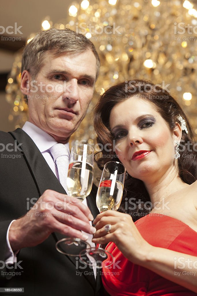 Couple toasting under chandelier stock photo