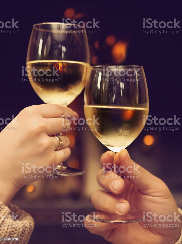 Couple toasting wineglasses in front of lit fireplace stock photo