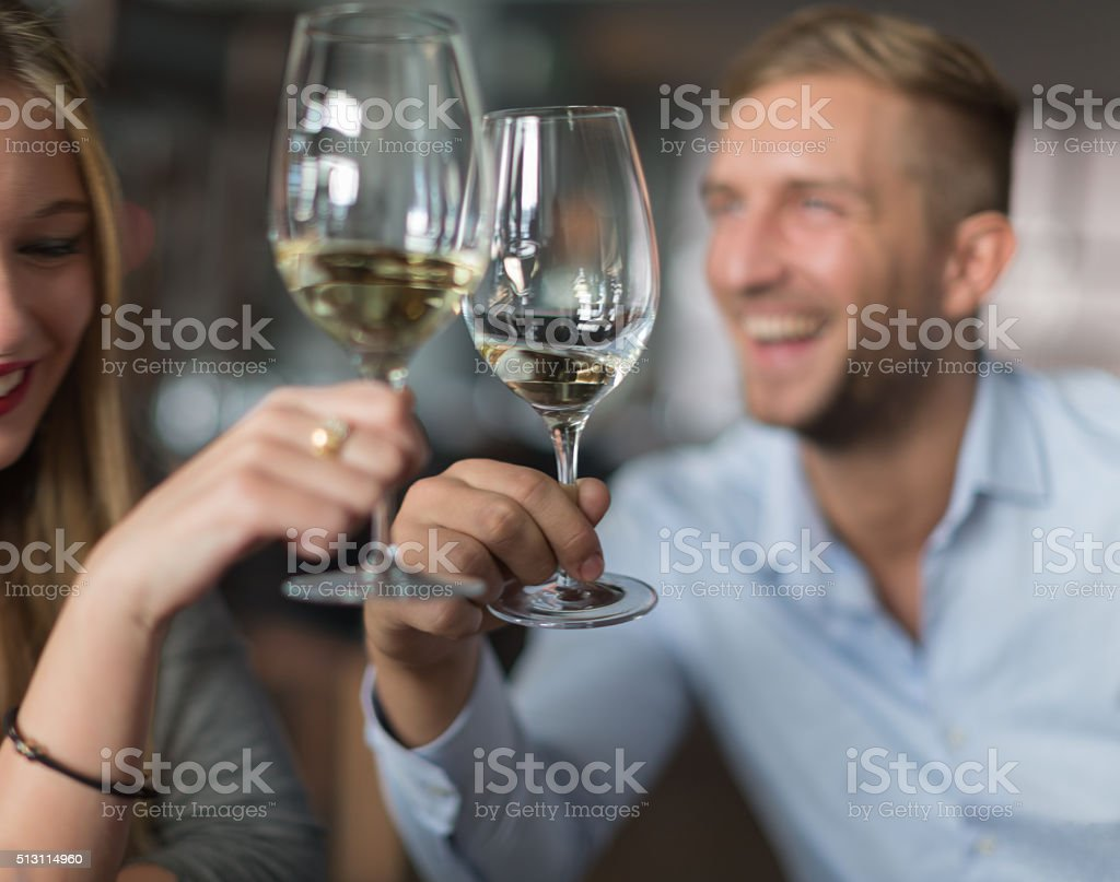 Couple toasting with white wine stock photo
