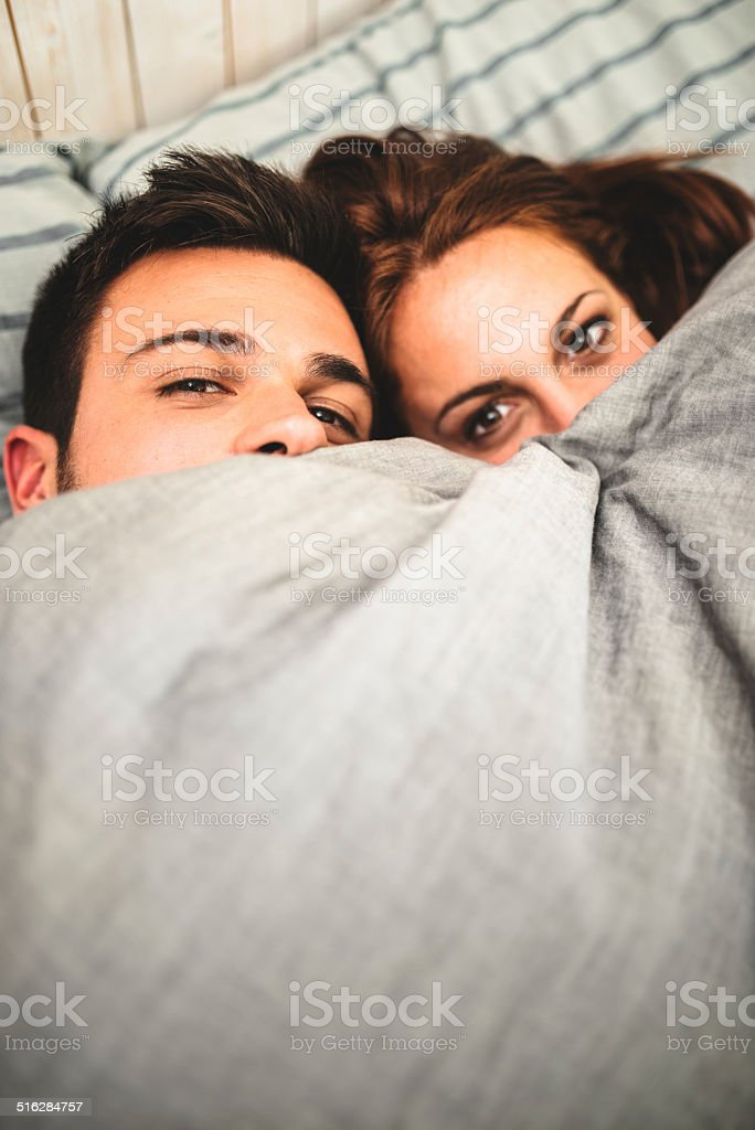 couple togetherness under the blanket stock photo