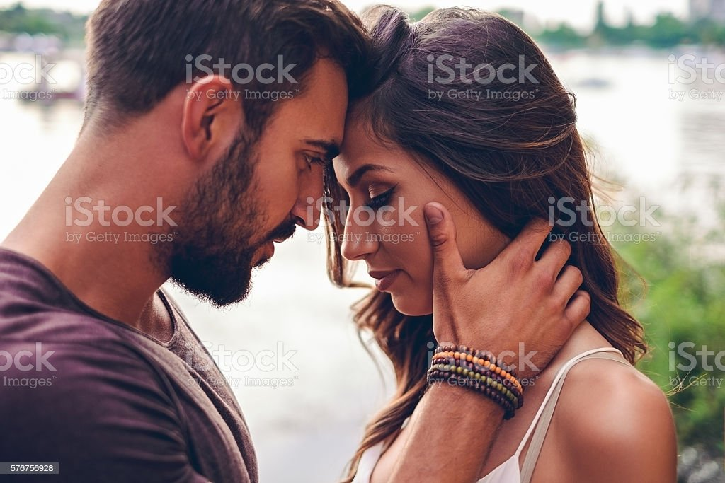 Couple touching with heads before kissing stock photo