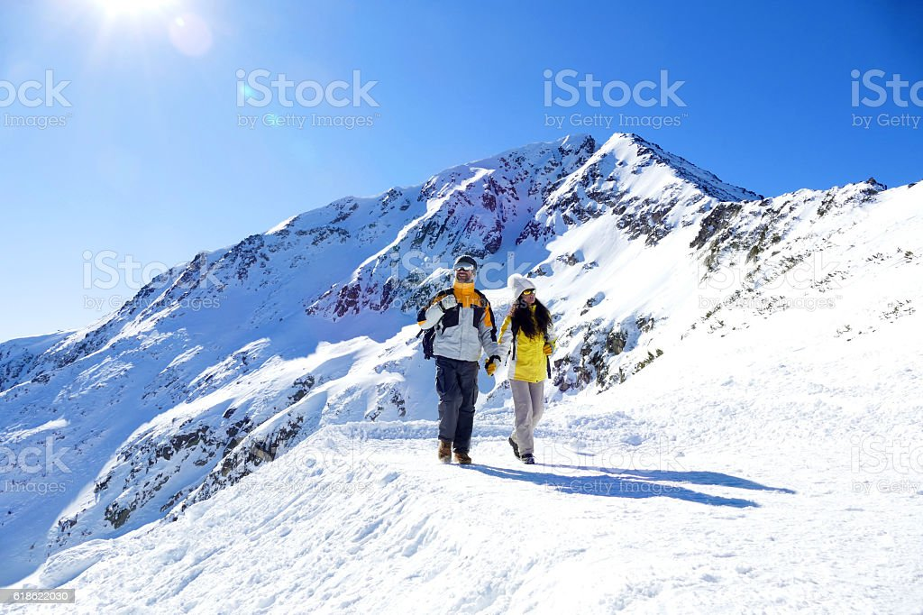 Couple tourists holding hands and walking on snow mountain stock photo