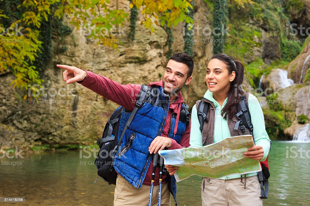 Couple tourists with the map pointing at something stock photo