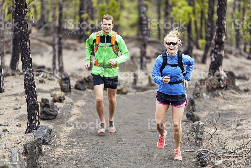 Couple trail running in forest royalty-free stock photo