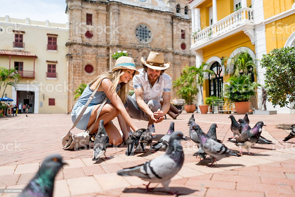Couple traveling and feeding doves in Cartagena stock photo