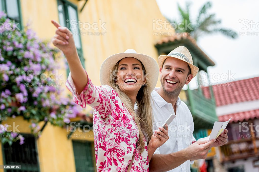 Couple traveling and pointing away stock photo