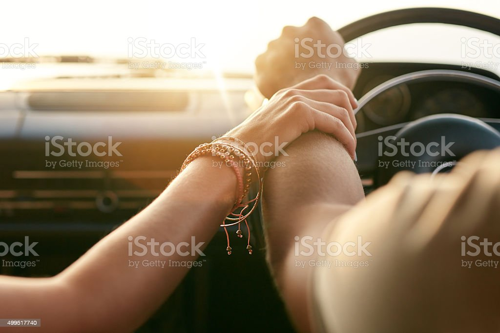 Couple traveling by car and holding hands stock photo