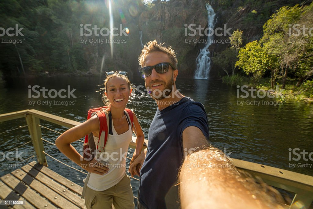 Couple traveling take selfie at the waterfalls stock photo