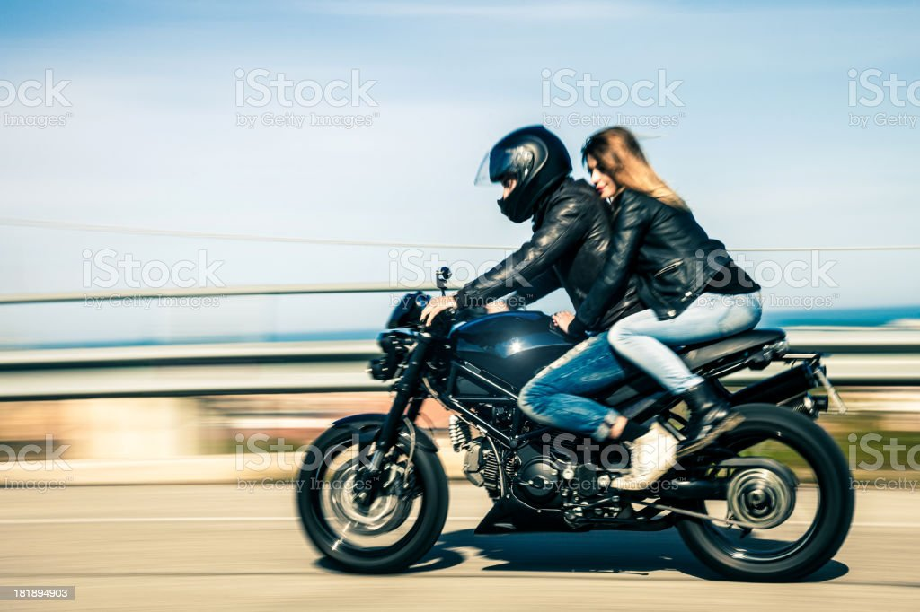 Couple travelling on a fast motorcycle stock photo