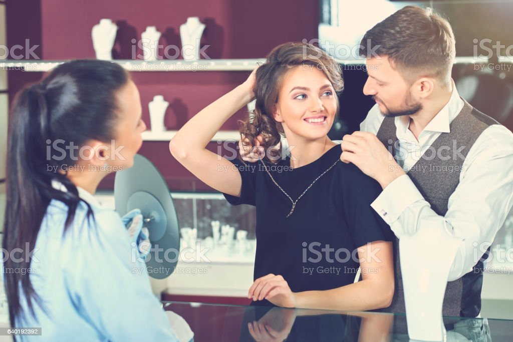Couple trying golden necklace at jewelry store. stock photo